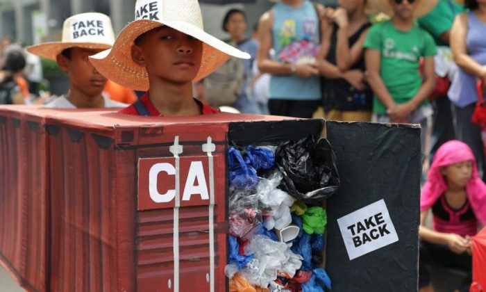 Filipino environmental activists wear a mock container vans filled with garbage to symbolize the 50 containers of waste that were shipped from Canada to the Philippines two years ago, at the Canadian embassy in Makati, south of Manila, Philippines, on May 7, 2015. (Aaron Favila/The Associated Press)