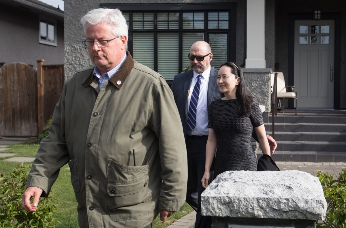 Huawei chief financial officer Meng Wanzhou, back right, is accompanied by a private security detail as she leaves her home to attend a court appearance in Vancouver on May 8, 2019. (The Canadian Press/Darryl Dyck)