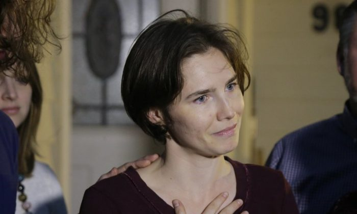 File photo showing Amanda Knox talking to reporters outside her mother's home, in Seattle, on March 27, 2015. Knox says she is returning to Italy for the first time since she was convicted and imprisoned, but ultimately acquitted, for the murder and sexual assault of her British roommate Meredith Kercher, in the university hilltop town of Perugia. (Ted S. Warren/AP Photo)