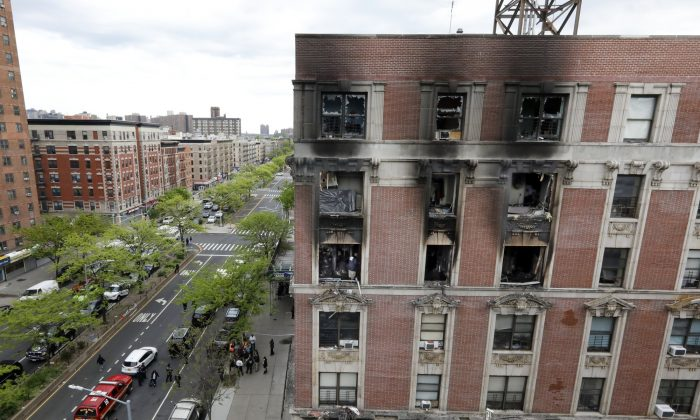 Fire marshals sift through a burned out apartment in New York's Harlem neighborhood on May 8, 2019. (Richard Drew/Photo via AP)