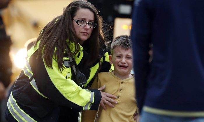 Officials guide students off a bus and into a recreation center where they were reunited with their parents after a shooting at a suburban Denver middle school in Highlands Ranch, Colo., on May 7, 2019. (David Zalubowski/AP Photo)