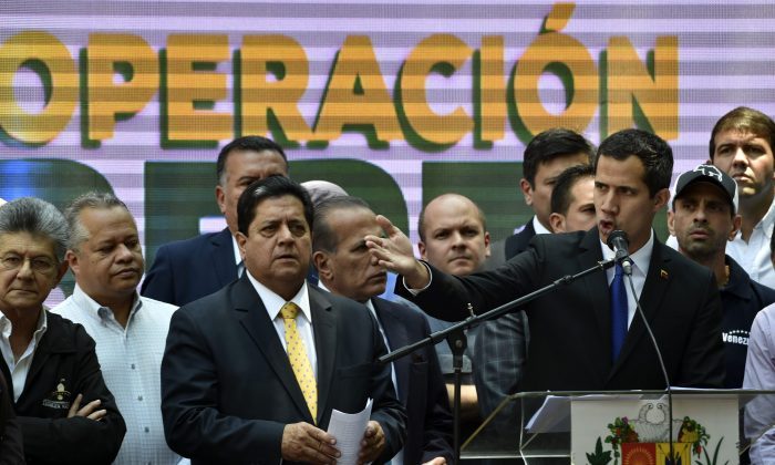 Venezuelan opposition leader Juan Guaido (R) speaks next to the vice-president of the Venezuelan National Assembly Edgar Zambrano (C) and its former president Henry Ramos Allup (L), in Caracas on March 27, 2019. (Yuri Cortez/AFP/Getty Images)