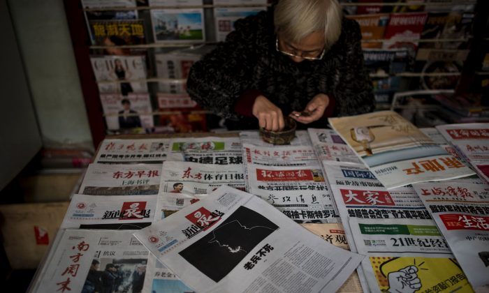 A seller shows Chinese newspapers at a news stand in Shanghai on November 27, 2016. 