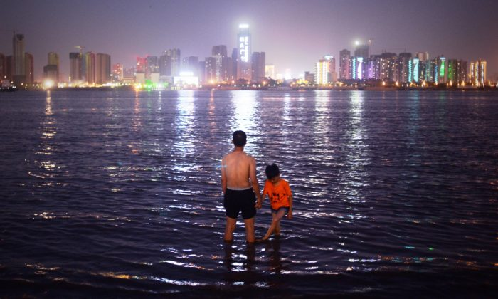 A man and his son standing in the Yangtze River in Wuhan. (Wang Zhao/AFP/Getty Images)