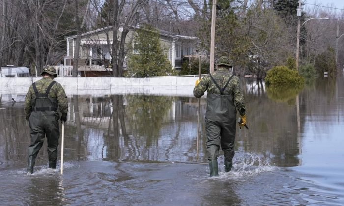 Two soldiers walk down a street in a flooded neighbourhood in Rigaud, Que., on April 29, 2019. (Paul Chiasson/The Canadian Press)
