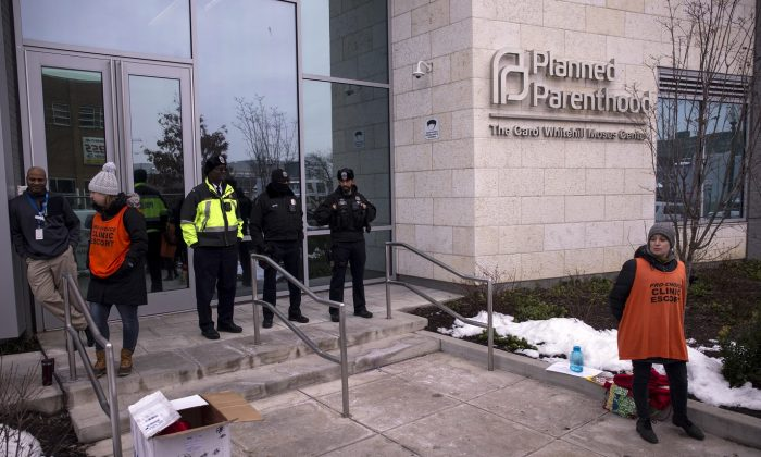 Police officers and clinic escorts stand outside of the Planned Parenthood of Metropolitan Washington during a protest vigil in Washington on Jan. 17, 2019. (Zach Gibson/Getty Images)