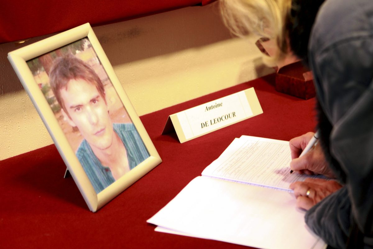 A woman signs condolence books in memory of Antoine de Leocour and Vincent Delory at Linselles' city hall, northern France