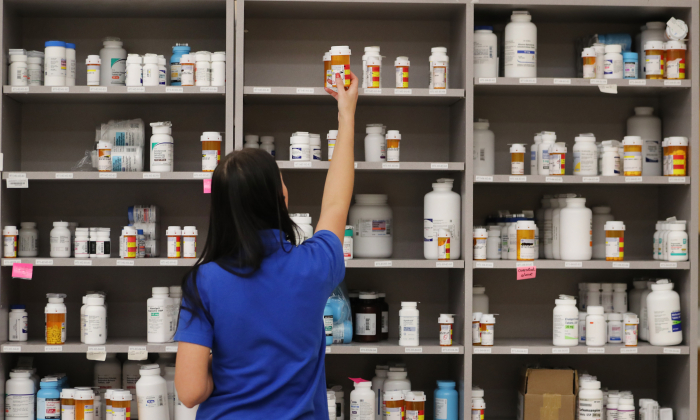 A pharmacy technician grabs a bottle of drugs off a shelf in a file photo. (George Frey/Getty Images)