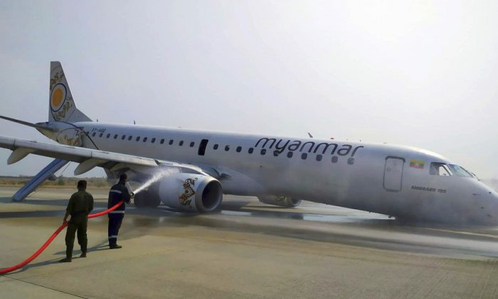 Firefighters work with hose on a plane of Myanmar National Airline (MNA) after an accident at Mandalay International airport in Mandalay, Myanmar on May 12, 2019. (Aung Thura via AP)