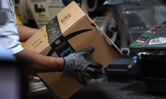 A worker assembles a box for delivery at the Amazon fulfillment center in Baltimore on April 30, 2019. (Clodagh Kilcoyne/Reuters/File Photo)