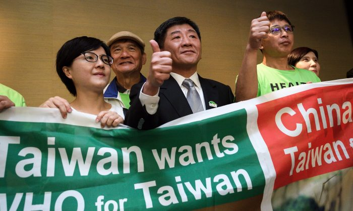 Taiwan's health Minister Chen Shih-chung (C) gives a thumb up as he poses with demonstrators after a press conference on the sideline of the World Health Organization annual Assembly on May 21, 2018 in Geneva. FABRICE COFFRINI/AFP/Getty Images)