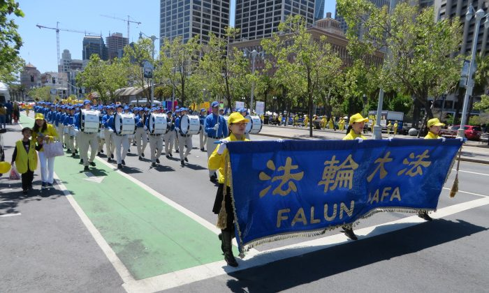 San Francisco Falun Dafa practitioners walk in a parade to celebrate World Falun Dafa Day on May 11, 2019. (Nathan Su/The Epoch Times)