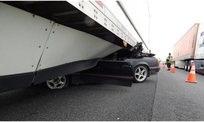 A wrecked mustang under a semi-trailer where it became wedged before being dragged for half a mile down the I-69 highway in Indiana on May 12, 2019. (Indiana State Police)