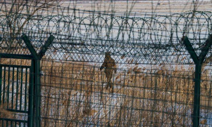 A North Korean soldier walks along the border fence of North Korean town of Sinuiju opposite the Chinese border city of Dandong in northeast China's northeast Liaoning Province, on Jan. 10, 2018. (Chandan Khanna/AFP/Getty Images)