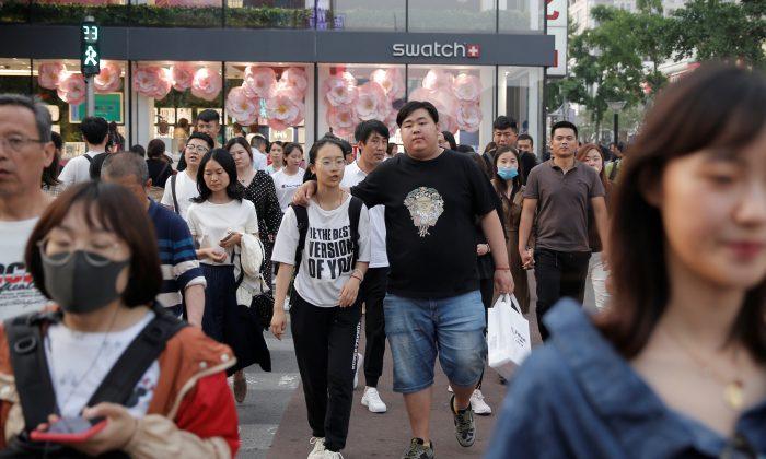 People walk in Wangfujing shopping street in Beijing on May 15, 2019. (Thomas Peter/Reuters)