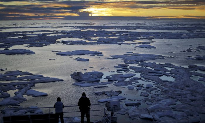 Researchers look out from the Finnish icebreaker MSV Nordica as the sun sets over sea ice in the Victoria Strait along theNorthwestPassagein the Canadian Arctic Archipelago. (AP Photo/David Goldman, File)
