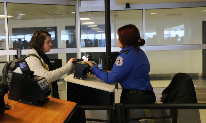A TSA agent checks a passengers documents on a security screening line at LaGuardia Airport in the Queens borough of New York City on Jan. 25, 2019.  (Photo by Spencer Platt/Getty Images)