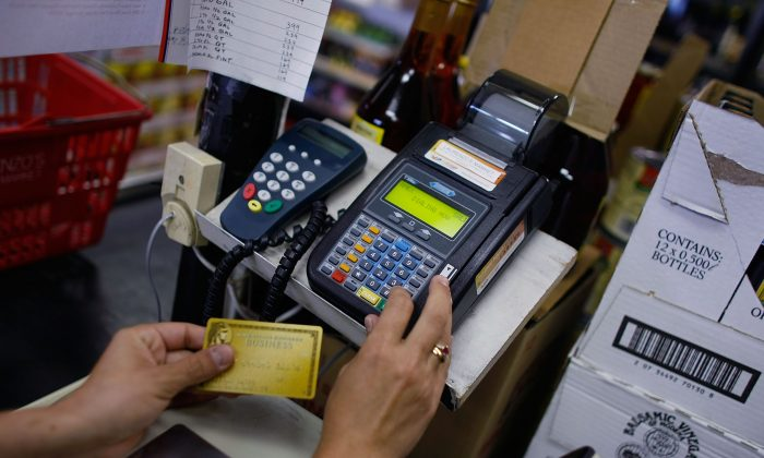 Yera Dominguez uses a credit card reader to charge a credit card from a customer for payment at Lorenzo's Italian Market in Miama, Fla., on May 20, 2009. Joe Raedle/Getty Images