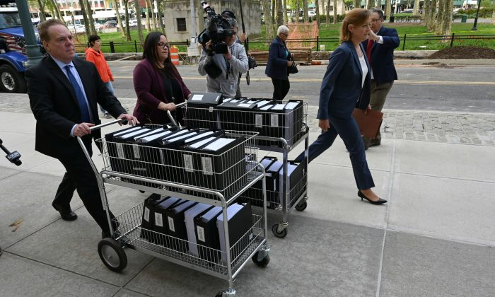 Members of the prosecution in the NXIVM case arrive with documents at Brooklyn Federal Court for day one of the trial of Keith Raniere, founder of NXIVM on May 7, 2019. (TIMOTHY A. CLARY/AFP/Getty Images)