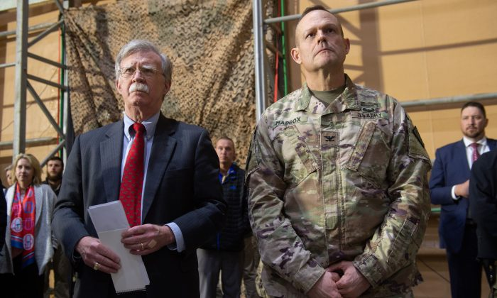 National security adviser John Bolton (L) listens as President Donald Trump speaks to members of the military during a trip to Al Asad Air Base in Iraq, on Dec. 26, 2018. (Saul Loeb/AFP/Getty Images)