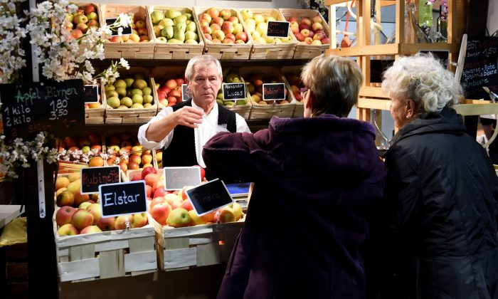A vendor sells apples in Berlin, Germany, in a file photo. The European Court of Justice has ruled that all employers must set up a system to record hours worked by staff.  (Tobias Schwarz/AFP/Getty Images)