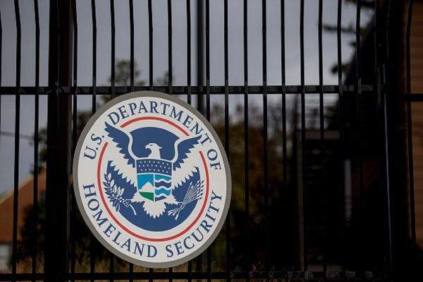 The U.S. Department of Homeland Security (DHS) seal hangs on a fence