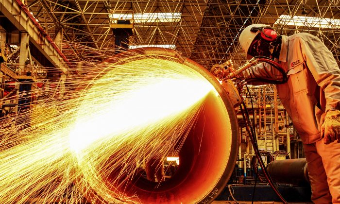 A worker cuts an oil pipe at a factory in Qingdao in China's eastern Shandong Province on Feb. 28, 2019. China's manufacturing activity shrunk for a third straight month in February, sinking to its worst performance in three years as the economy slows and the U.S. trade war bites, official data showed on Feb. 28. (STR/AFP/Getty Images)