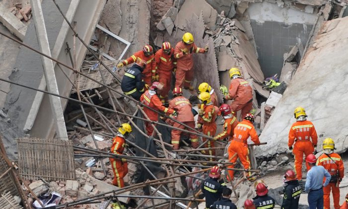 Firefighters work at the site where a building collapsed, in Shanghai, China on May 16, 2019. (Aly Song/Reuters)