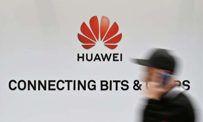 A visitor walks past the logo of Chinese telecom giant Huawei at the Hanover Messe technology fair on April 1, 2019, in Hanover Germany. (John MacDougall/AFP/Getty Images)
