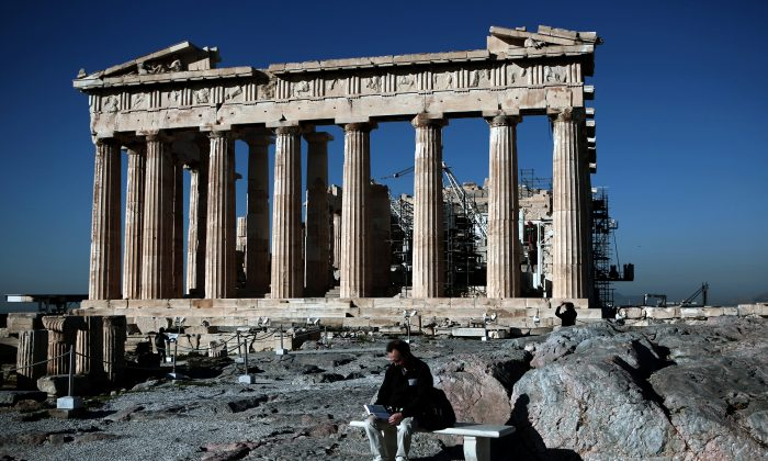 A man reads a book in front of the Parthenon temple on the Acropolis hill in Athens on Feb. 21, 2015. (ANGELOS TZORTZINIS/AFP/Getty Images)