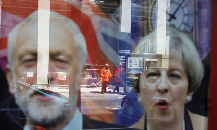 Workers in protective equipment are reflected in the window of a betting shop with a display inviting customers to place bets on the result of the general election with images of Britain's Prime Minister Theresa May and opposition Labour Party leader Jeremy Corbyn, in London on June 7, 2017. (Marko Djurica/Reuters)
