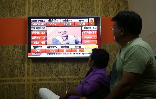 Men look at a television screen showing exit poll results