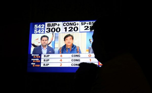 A man looks at a television screen showing exit poll results