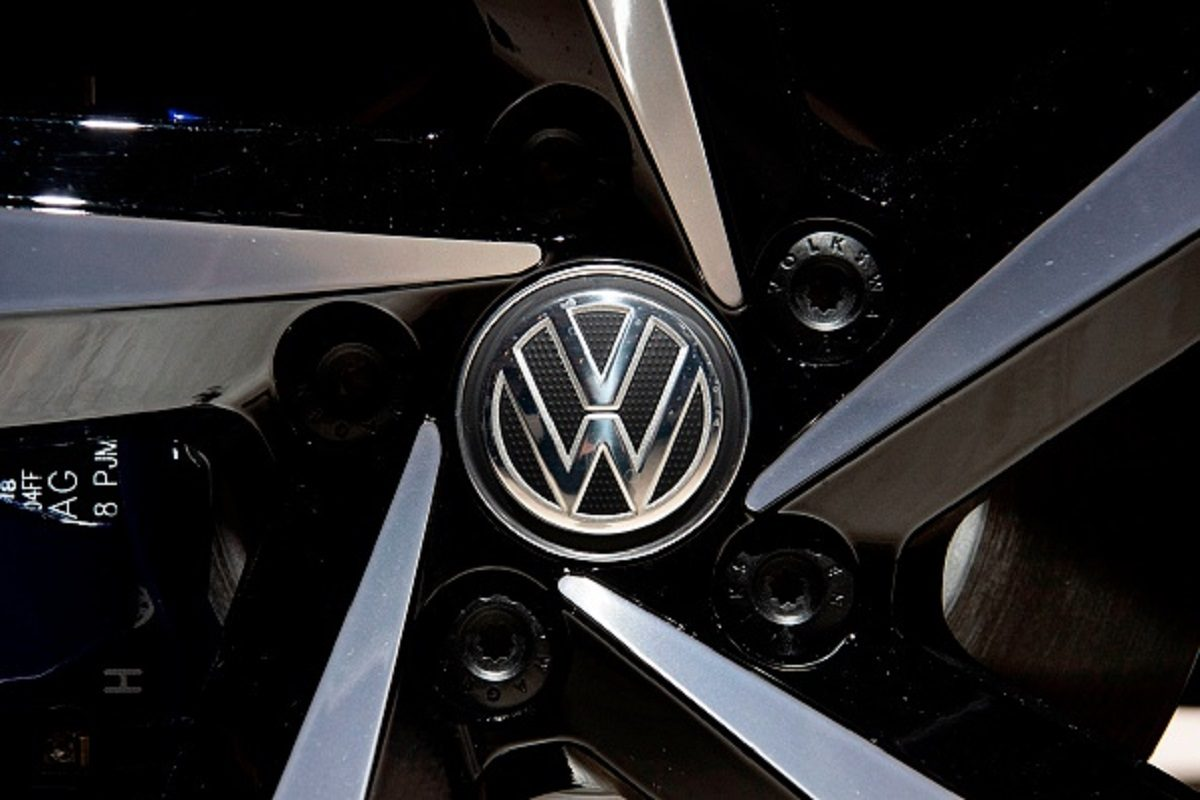 A Volkswagen logo appears on the wheel of a VW Passat GTE Variant on display