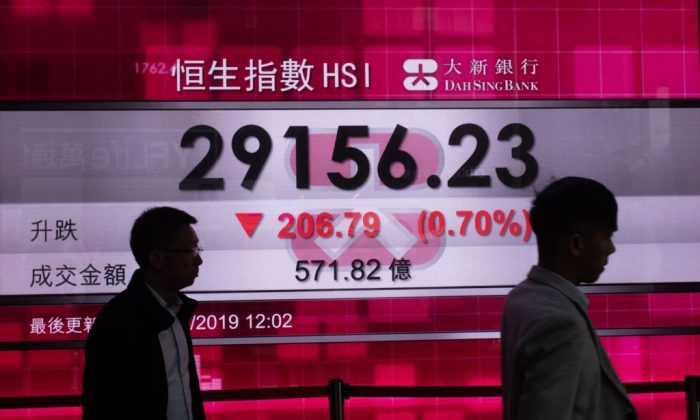 Pedestrians walk in front of a stock display board that shows the Hang Seng Index in Hong Kong on May 8, 2019 (PHILIP FONG/AFP/Getty Images)
