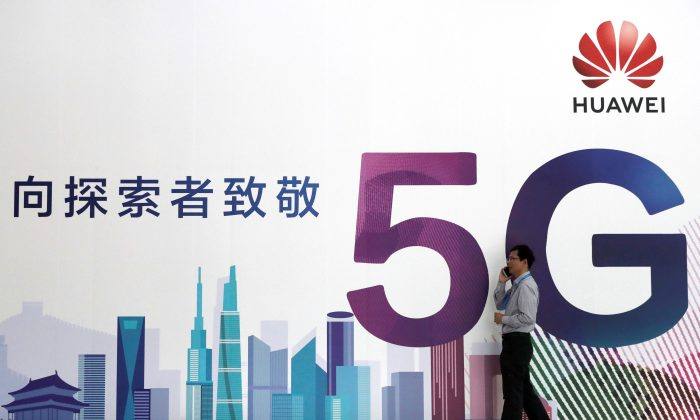 A man talks on his mobile phone beside Huawei's billboard featuring 5G technology at the PT Expo in Beijing on Sept. 26, 2018. (Reuters)
