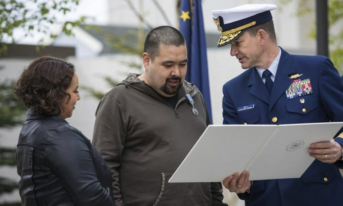 """Rear Adm. Matthew Bell (R), presents a Silver Lifesaving Medal to George """"Radar"""" Lambert, middle, at the Atwood Building courtyard in Anchorage, Alaska, on May 18, 2019. (Loren Holmes/Anchorage Daily News via AP)"""