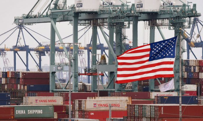 International shipping containers beside a U.S. flag at the Port of Los Angeles in Long Beach, Calif., on May 14, 2019. (Mark Ralston/AFP/Getty Images)