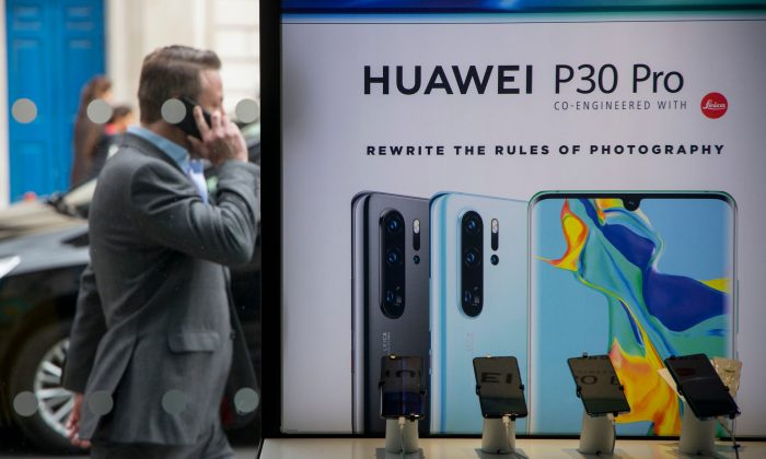 A pedestrian walks past a Huawei product stand in London, on April 29, 2019.   (Tolga Akmen/AFP/Getty Images)