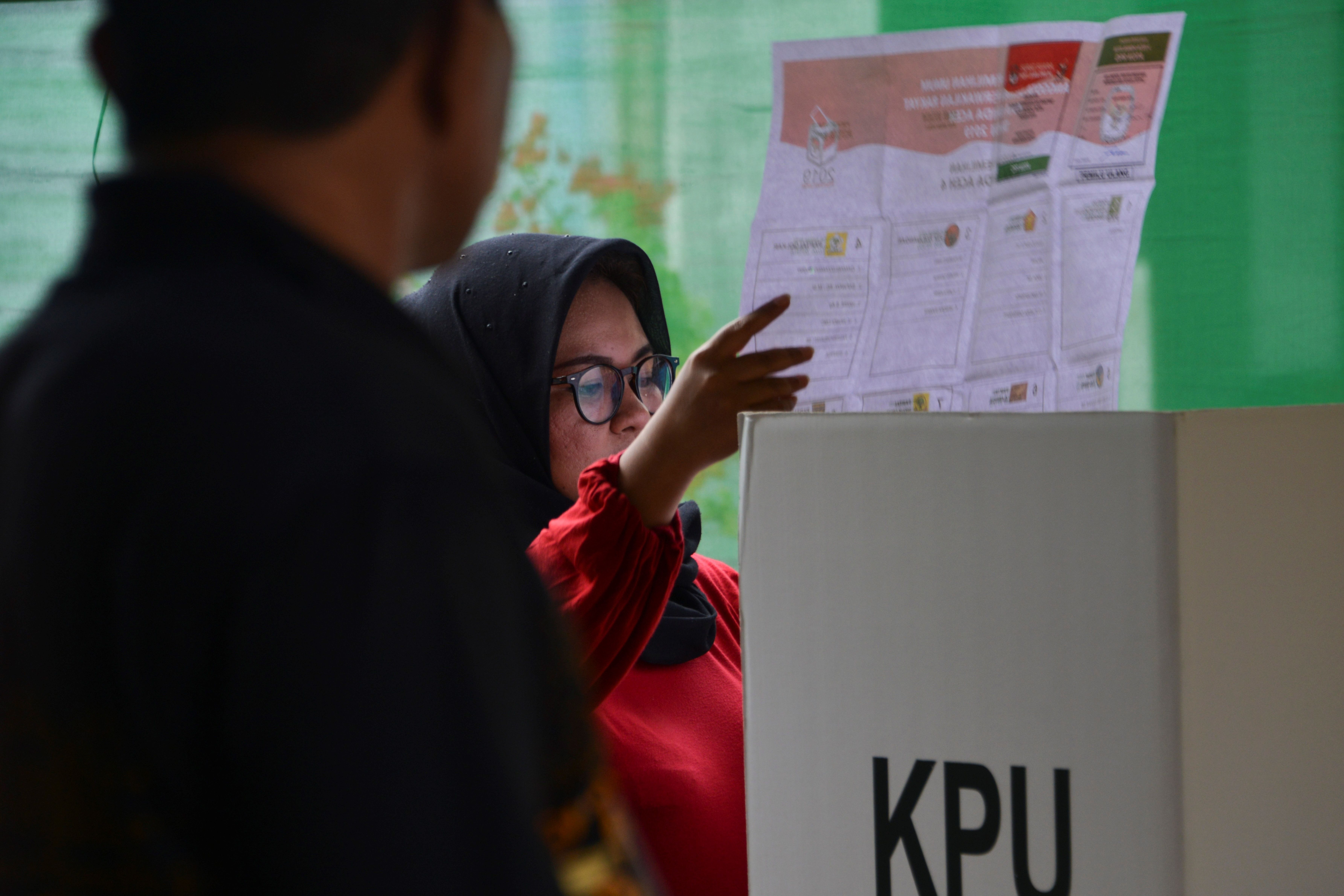 A woman looks at her ballot