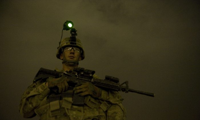A sergeant of the US Army operating under NATO keeps vigil during a night-time operating post at Devils hill, Afghanistan on Sep. 6, 2012. Prosecutors allege the defendant sold counterfeit uniforms and gear to the U.S. military. (Photo credit should read TONY KARUMBA/AFP/GettyImages)