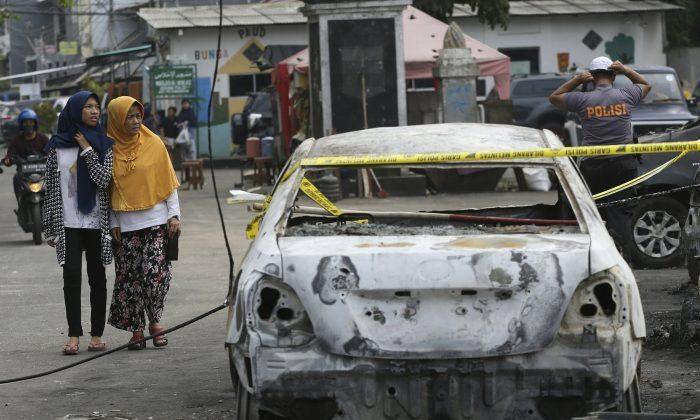 Muslim women walk near a burnt car in Jakarta, Indonesia, on May 22, 2019. (Achmad Ibrahim/AP Photo)