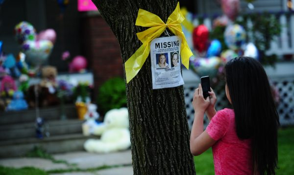 A girl takes a picture of a missing person sign displaying portraits of Amanda Berry, one of the three women held captive for a decade, in front of her sister's house in Cleveland, Ohio
