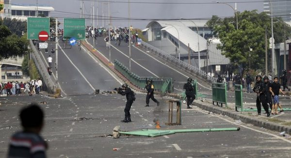 Indonesian police take position during a clash with supporters of Indonesian presidential candidate Prabowo Subianto