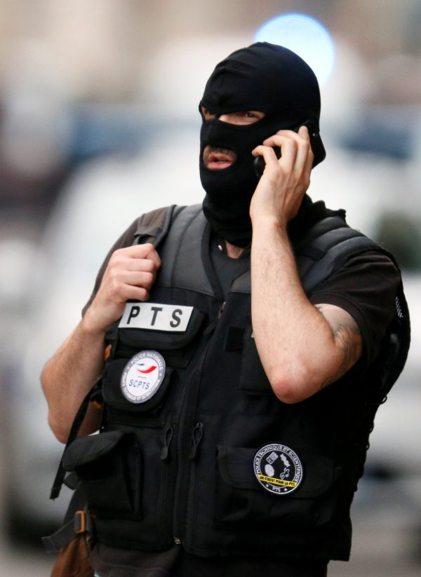 Police officer is seen on his mobile phone near the site of a suspected bomb attack in central Lyon