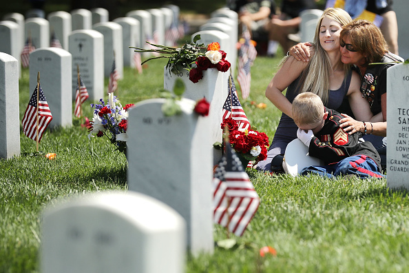 Brittany Jacobs (L) of Hertford, North Carolina, and her son, Christian Jacobs, 6, are embraced by a friend while sitting next to the grave of Brittany's husband, U.S. Marine Corps Sgt. Chris Jacobs, in Section 60 at Arlington National Cemetery on Memorial Day May 29, 2017 in Arlington, Virginia. (Chip Somodevilla/Getty Images)