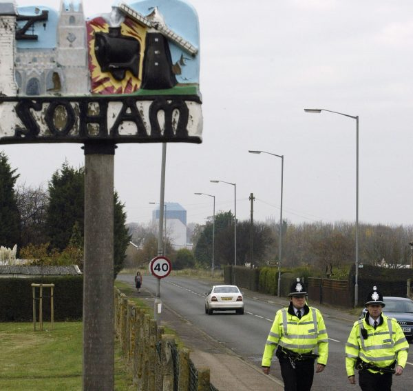 officers walking past Soham sign
