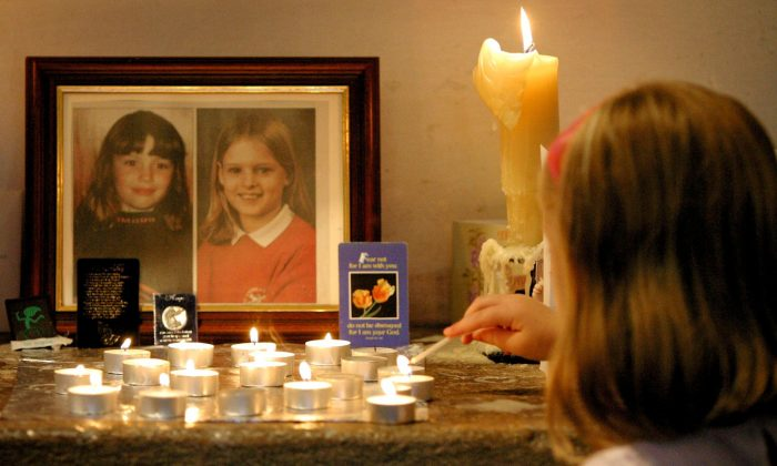 A young girl lights a candle after attending a special service for the slain ten-year-old schoolgirls Jessica Chapman and Holly Wells at St Andrew's church in Soham, on Aug. 18, 2002. (Dan Chung/AFP/Getty Images)