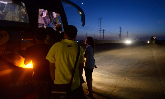 Passengers getting onto a bus at night. (Ed Jones/AFP/Getty Images)