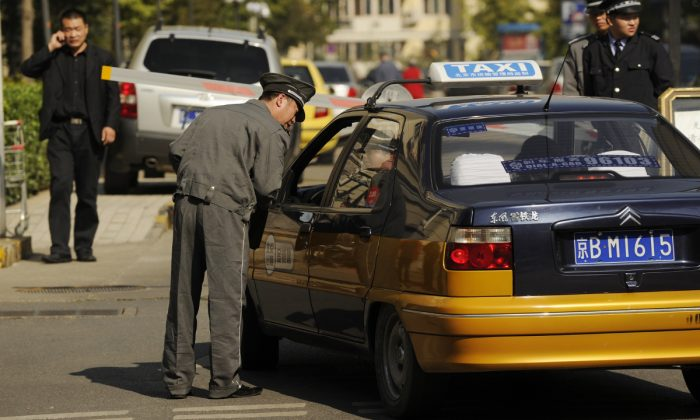 A guard speaking to a taxi driver. (Peter Parks/AFP/Getty Images)